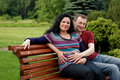 Young happy couple (pregnant woman) on bench Royalty Free Stock Photo