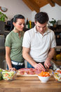 Young happy couple preparing lunch in kitchen Stock Photography