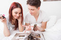 Young happy couple reading magazine together in bed smiling Royalty Free Stock Photo