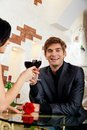 Young happy couple romantic date drink glass of red wine at restaurant celebrating Stock Photo