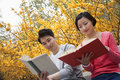 Young happy couple sitting on a park bench reading books springtime in the park Stock Photo