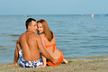 Young happy couple sitting on sandy beach and embracing smiling summer sea background Royalty Free Stock Images