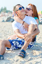 Young happy couple sitting on sea beach and embracing smiling sandy outdoors Royalty Free Stock Photography