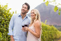 Young happy couple smiling and looking in the distance grape fields Royalty Free Stock Photo