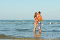 Young happy couple together on sandy beach embracing outdoors Royalty Free Stock Photo