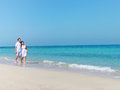 Young happy couple walking on the beach smiling holding around each other Royalty Free Stock Photos