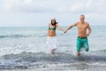 Young happy couple walking on beach sunset holiday Royalty Free Stock Images