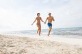 Young happy couple walking on beach sunset holiday Stock Photo