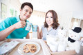 Young happy couples in domestic kitchen with breakfast Royalty Free Stock Photography