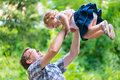 Young happy dad playfully tosses his little daughter in the sky Stock Photo