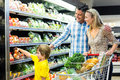 Young happy family with their son at supermarket Royalty Free Stock Image