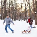 Young happy family in winter park baby on the sled the snow Stock Photography