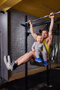 Young happy father doing pull ups on the bar with son on his legs at the cross fit gym against brick wall.