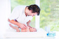 Young happy father playing with his newborn baby son while changing a diaper Royalty Free Stock Photos