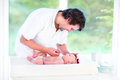Young happy father playing with his newborn baby son while changing a diaper Royalty Free Stock Images