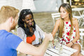 Young and happy friends sitting talking at a table outdoors smiling Stock Photography