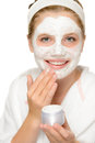Young happy girl putting facial mask cleaning face treatment Royalty Free Stock Photo