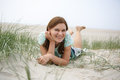 Young happy girl relaxing on sand dunes of the beach of st peter ording north sea germany Royalty Free Stock Image