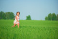 Young happy girl running at green wheat field with her friend together Royalty Free Stock Image