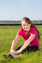 Young happy girl stretching in park on the grass Royalty Free Stock Photo