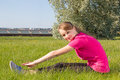 Young happy girl stretching in park on the grass Stock Photos