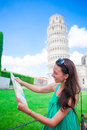 Young happy girl with toristic map on travel to Pisa. Tourist traveling visiting The Leaning Tower of Pisa. Royalty Free Stock Photo