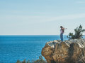 Young happy girl traveler standing on rock over sea, Turkey Royalty Free Stock Photo
