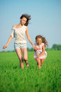 Young happy girls running at green wheat field Stock Photography