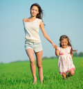 Young happy girls running at green wheat field down with her friend together Royalty Free Stock Photos