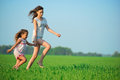 Young happy girls running at green wheat field down with her friend together Stock Images