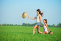 Young happy girls running witch baskets at green wheat field with basket with her friend together Stock Photo