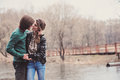 Young happy loving couple kissing on the walk in early spring at river side Stock Photos