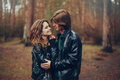 Young happy loving couple in leather jackets hugs outdoor on cozy walk in forest autumn Stock Photos