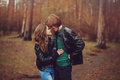 Young happy loving couple in leather jackets hugs outdoor on cozy walk in forest autumn Stock Image