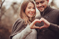 Young happy loving couple showing heart for valentine day on cozy outdoor walk in forest Royalty Free Stock Photo