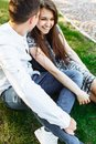 Young, happy, loving couple, sitting together on the grass in the Park, and enjoying each other, advertising, and inserting text Royalty Free Stock Photo