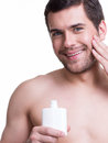 Young happy man applying cream. Stock Photo