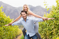 Young happy man carrying happy woman on his back men women in the grape fields Royalty Free Stock Images