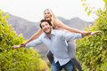 Young happy man carrying happy woman on his back men women in the grape fields Stock Images