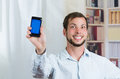 Young happy man holding his cell phone and showing the screen copy space Royalty Free Stock Photos