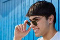 Young happy man holding sunglasses smiling Royalty Free Stock Photo