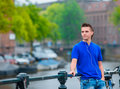 Young happy man listening to music background of canal in Amsterdam, Netherlands Royalty Free Stock Photo