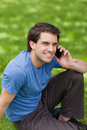 Young happy man using his mobile phone while sitting on the gras Stock Photography