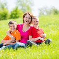 Young happy mother with children in park outdoor portrait Stock Photography