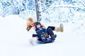 Young happy mother and her son on sleigh ride adorable having fun together a in a snowy forest Royalty Free Stock Images