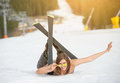 Young happy naked female skier is lying on snowy slope near ski lift at ski resort Royalty Free Stock Photo