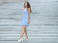 Young happy playful woman in light striped white blue dress posing at concrete stairway outdoor Royalty Free Stock Photo