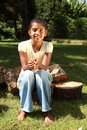 Young happy school girl outdoors sitting on logs Royalty Free Stock Photos