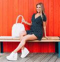 Young happy smiling blonde tan woman posing outdoor in summer time wearing vintage dress, sitting at wooden bench at red backgroun Royalty Free Stock Photo