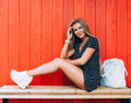 Young happy smiling blonde tan woman posing outdoor in summer time wearing vintage dress and white sneakers with big handbag sitti Royalty Free Stock Photo
